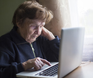 Old woman works (learning to work) on laptop in her house.